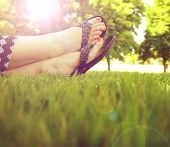 stock photo of painted toes  - pretty feet on grass at sunset with nails painted and sandals on - JPG