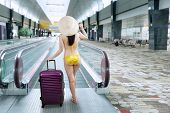 Woman Walking To Escalator Wearing Bikini