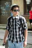 Modern young boy with headphones and sunglasses