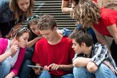 Group of teenagers with tablet computer outside