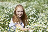 Beautiful young woman sitting in a field of chamomile