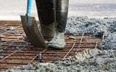 image of work boots  - person with gum boots on working in spreading ready mix concrete - JPG