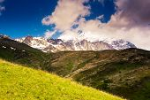 Majestic view of alpine meadows with blue sky at the foot of Tetnuldi glacier. Upper Svaneti, Georgi