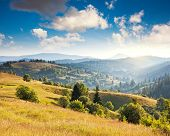 Fantastic sunny hills under morning cloudy sky. Dramatic overcast sky. Carpathian, Ukraine, Europe.