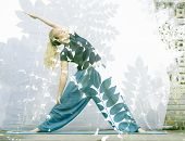 Double exposure portrait of attractive woman performing yoga asana combined with photograph of plant