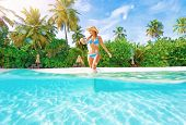 Woman comes into water on the beach, beautiful tropical island, luxury summertime vacation, happines