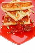 russian food - meat wrapped in a pancake with red hot pepper and pickled mushrooms served on red pla
