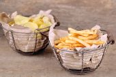 Tasty french fries in metal basket and potato chips on wooden table