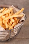 Tasty french fries in metal basket on wooden table
