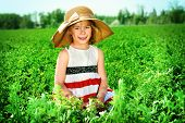 Charming little girl on a meadow in summer day. Happy childhood. Child fashion.