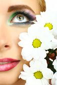 Beautiful woman with bright make-up and flower, close up