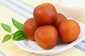 stock photo of jamun  - Gulab jamun dessert on bamboo mat, closeup