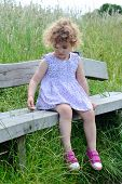 Child on a bench outdoors.