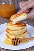 Pancakes with honey in hand