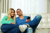 lovely young couple sitting on the sofa and watching TV