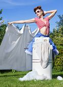 Pin up style photo of woman with vintage wringer washing machine