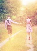 Loving couple in traditional Bavarian clothes walking together in countryside