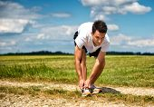 Sportsman on a rural track in open countryside bending over tying his laces on his running shoes before commencing his workout and training