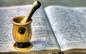 stock photo of pestle  - Old pharmacy book with mortar and pestle - JPG