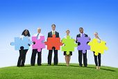 Group of business people holding puzzle pieces.