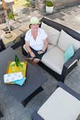 picture of settee  - Friendly attractive senior woman sitting on a comfortable wicker settee on an outdoor paved patio with a tray of chilled drinks on the table looking up to smile happily at the camera above - JPG