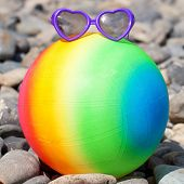 Colorful Beach Ball With Sunglasses On The Pebbles.