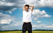 Man stretching his muscles before training standing against a cloudy blue sky in the countryside wit