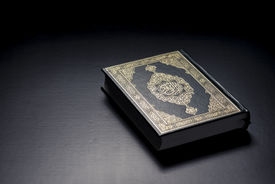image of islamic religious holy book  - Islamic Holy Book Quran Under Soft Light on Black Background - JPG