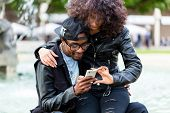 image of fountains  - African American man sitting with girlfriend at fountain showing message on mobile phone or looking up information  - JPG