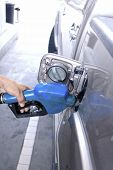 image of vacuum pump  - Blue fuel nozzle in pouring to car - JPG