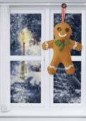 Gingerbread man decoration hanging in the window with snow scene outside