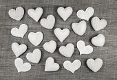 Shabby chic decoration: white hearts on wooden white grey background.