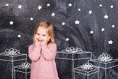 foto of little girls photo-models  - Little girl stands near the gift and smiling - JPG