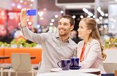sale, shopping, consumerism, technology and people concept - happy young couple with smartphone taking selfie and drinking coffee or tea at cafe in mall