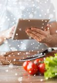 cooking, people, technology and home concept - closeup of man reading recipe from tablet pc computer and vegetables on table in kitchen