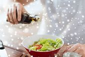 cooking, people, food and home concept - close up of male hands flavoring salad in a bowl with olive oil