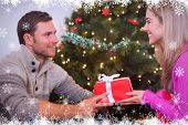 Sitting couple giving each other presents against fir tree forest and snowflakes