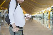 Pregnant Touching Phone In Airport