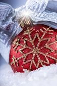 Christmas red ball or candle with goden ornaments,silver ribbon and snow.