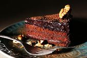 Delicious chocolate cake on plate on dark background