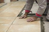Home improvement, renovation - construction worker tiler is tiling floor