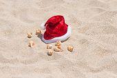 Santa Hat And Sea Shells On The Beach