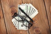 Money cash, glasses and pen on wooden table