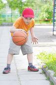 Постер, плакат: Маленький мальчик дриблинг баскетбол