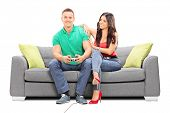 Girl watching her boyfriend play video game seated on a sofa isolated on white background