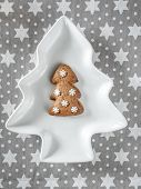 Home-made christmas gingerbread tree-shaped cookie on white plate