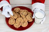 Closeup of Santa Claus with a plate full of chocolate chip cookies and a glass of milk.