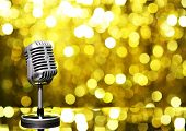 Silver microphone on golden background