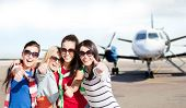 travel, holidays, vacation, happy people concept - smiling teenage girls or young women showing thumbs up at airport