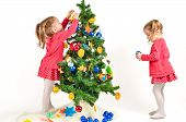 pic of twin baby girls  - Twin Girls are decorating Christmass Tree with home made Ornaments isolated on white Background - JPG